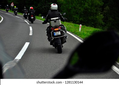 motorcycle group, bikers riding travelling in formation trough Slovenia, touring the Alps, beautiful landscapes, adventure motorcycles, summer time, mountain background, view from the back