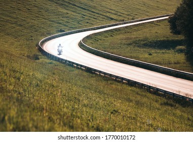Motorcycle with headlight moving by the highway illuminated with back evening sun light. Safety solo traveling concept image.