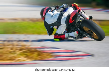 Motorcycle leaning into a fast corner on race track