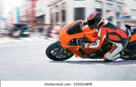 Motorcycle leaning into a fast corner in downtown
