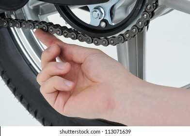 motorcycle mechanic checking the tension on a chain
