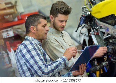motorcycle mechanic repairing engine under supervisors guidance