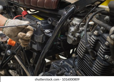 motorcycle mechanic replaces a battery. (maintenance) selective focus