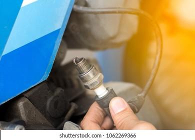 Motorcycle mechanic replacing glow plug  in bike engine,spark plug replacement work in repair shop.