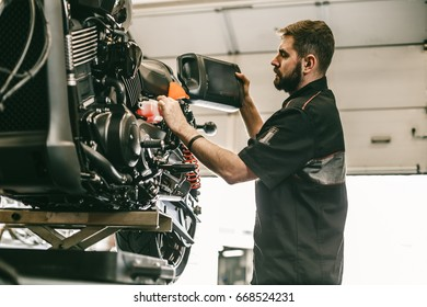 Motorcycle mechanic replacing and pouring fresh oil into engine at maintenance repair service station. Portrait of an auto mechanic putting oil in a car engine.