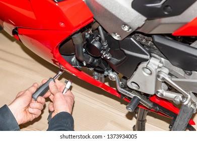 Motorcycle mechanic screwing on the fairing of a motorcycle - Serie Repair Workshop