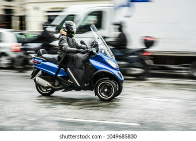 A motorcycle on road in big city. Motorbike or scooter on three wheels on road in motion.