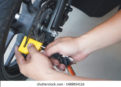 Motorcycle owner use a disc brake lock on a motorbike or scooter .Motorcycle Security and Anti-Theft Systems