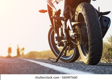 A motorcycle parking on the road right side and sunset, select focusing background.