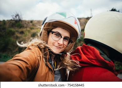 Motorcycle passenger, young attractive blonde woman with glasses and open face helmet with visor, in brown leather jacket makes selfie on action camera while riding on back of motorbike