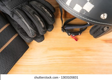 Motorcycle protective gear - helmet, gloves and kidney belt on a wooden background. Flat lay top view. Copy space on the bottom right corner.