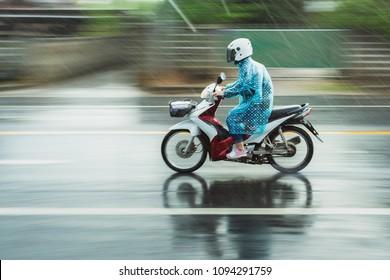 Motorcycle raincoat In the rain,people drive motorbike in rain day blur.