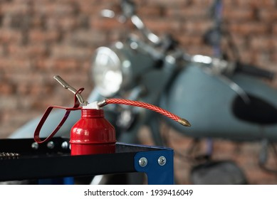 Motorcycle repairing service concept background. A red oil can on the workbench on the old garage background.