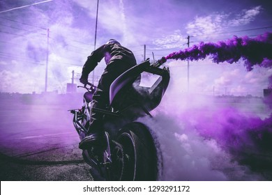 Motorcycle rider doing a burnout with purple smoke moving away from camera.