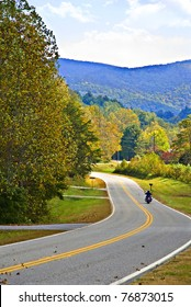 A motorcycle rider on a mountain highway surrounded by autumn colors.