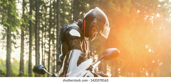 motorcycle rider prepares for ride on the forest road.
