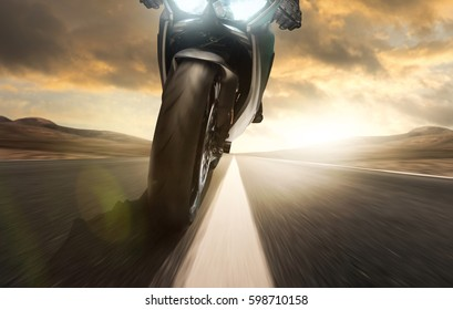 Motorcycle rides on a country road at sunset