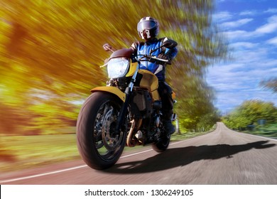 motorcycle riding on highway through countryside besides birches. fast motorbike on empty country road in the forest. rider enjoys freedom