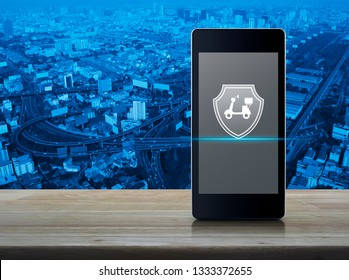 Motorcycle with shield flat icon on modern smart mobile phone screen on wooden table over city tower, street, expressway and skyscraper, Business motorcycle insurance online concept