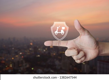 Motorcycle with shield flat icon on finger over blur of cityscape on warm light sundown, Business motorbike insurance concept