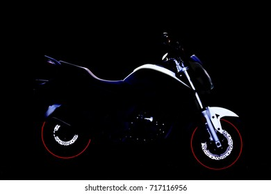 motorcycle standing in the dark with light on top