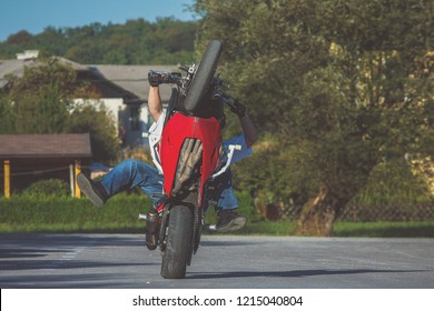 Motorcycle stunt man practicing on a home parking lot on a red and white motorcycle. Frontal view of a stuntman making a wheelie on a motorcycle.