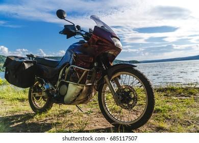 Motorcycle at sunset at lake. off road touring adventure travel enduro active lifestyle