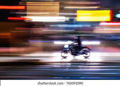 motorcycle that travels fast in the night lit streets of a metropolitan city