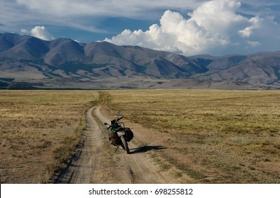 Motorcycle traveler standing on extreme rocky steppe road path in a mountain plateau in cloudy weather on the background of hills Altai Mountains Siberia Russia