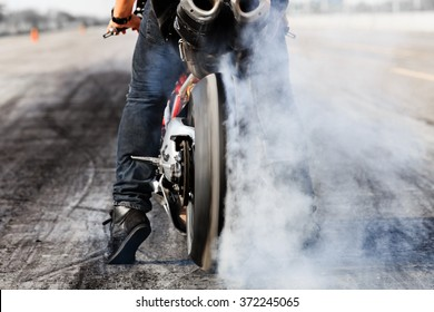Motorcycle wheel burning tires and smoking on race track, prepare for race.