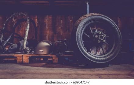 Motorcycle wheel on the floor with workshop tools, vintage garage, with blank copy space