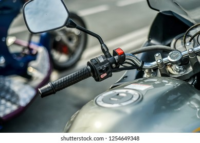 Motorcycles on the background of the city. Beautiful and stylish control panel and steering wheel of a modern motorcycle at close range against the background of the city.
