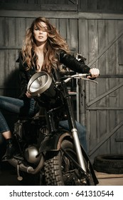 Motorcycling, hobby and lifestyle, Pretty girl biker or sexy woman with blond, long hair in leather jacket sitting on vintage motorcycle, bike, in garage on grey wooden background.