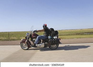 Motorcyclist with American flag bandana driving towards Sturgis South Dakota for the 67th Annual Sturgis Motorcycle Rally, Sturgis, South Dakota, August 6-12, 2007