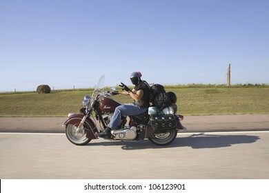 Motorcyclist with American flag bandana flashing peace sign as he heads west towards Sturgis South Dakota for the 67th Annual Sturgis Motorcycle Rally, Sturgis, South Dakota, August 6-12, 2007
