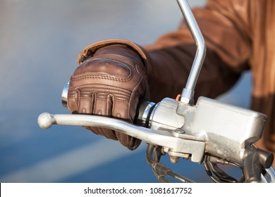 Motorcyclist arm in brown leather glove holds twist grip throttle, close up view