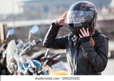 Motorcyclist Caucasian woman sets her full-face helmet, portrait against bikes background, copyspace