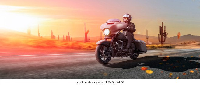 motorcyclist cruising his touring chopper on a highway in the desert at sun dawn enoy his personal freedom. copy space on the left.
