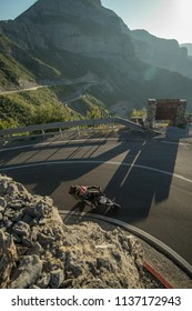 Motorcyclist driving and leaning into a curve on a famous albanian mountain road SH20, full of hairpins and tight turns at early evening.