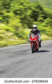 Motorcyclist driving on country road, speed blurred effect and copy space.