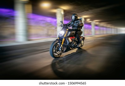 Motorcyclist in full black leathers and helmet riding fast through tunnel with columns and purple light in background