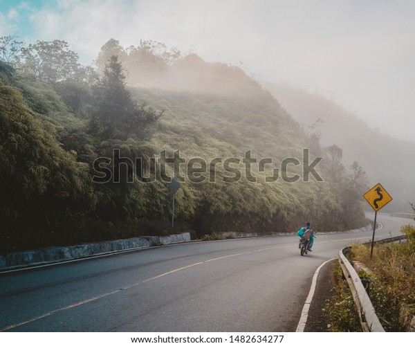Motorcyclist going down a curved road and traffic signal.