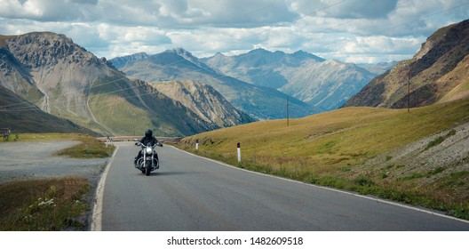 A motorcyclist is going through the Stelvio Pass. Italy