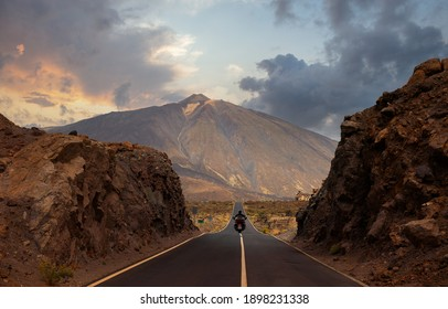 A motorcyclist has passed through a gorge and is driving on the straight and hilly road towards Mount Teide on the island of Tenerife. It is just before sunset in the evening.