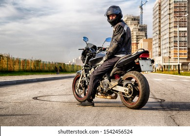A motorcyclist in a helmet and a biker jacket with a raised visor sits on a sports bike sideways to the audience.