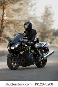 Motorcyclist in a helmet on a motorcycle on a country road. Guy driving a bike during a trip. Riding a modern sports motorcycle on the highway
