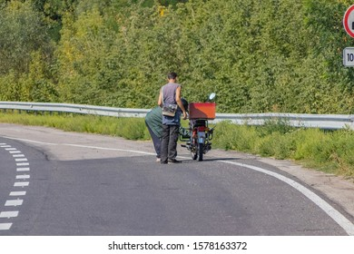 A motorcyclist inflates a broken wheel by the highway. On the track of Asian bikers, the wheel was damaged. Men repair and pump up a damaged wheel on a moped to continue driving to their destination
