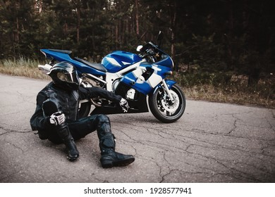 Motorcyclist in leather outfit and a black helmet sits on the road next to a sports bike