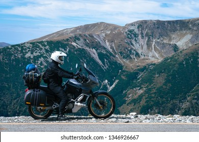 Motorcyclist man and Adventure Motorbike on the top of the mountain. Motorcycle trip. World Traveling, Lifestyle Travel vacations sport outdoor concept, copy space. Transalpina Romania