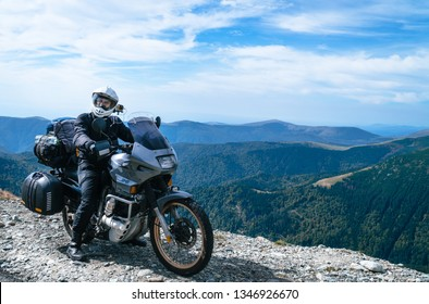 Motorcyclist man and Adventure Motorbike on the top of the mountain. Motorcycle trip. World Traveling, Lifestyle Travel vacations sport outdoor concept, copy space. Transalpine Romania